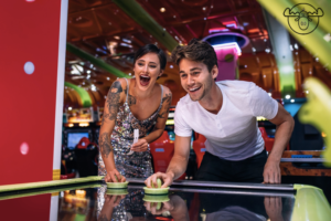 Two adults playing air hockey