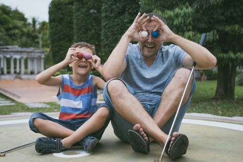 Man and child acting silly with golf balls