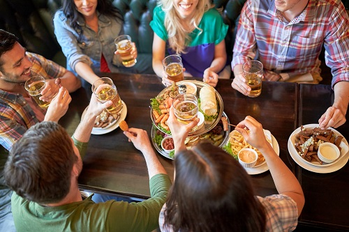 Friends gathered around a table with food and drinks