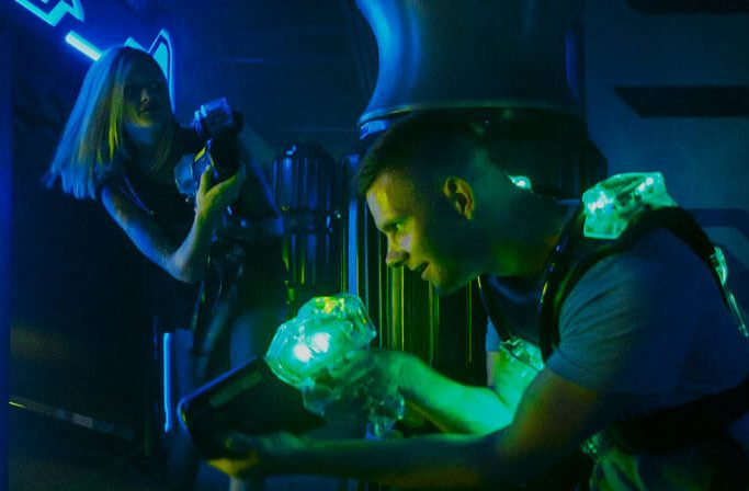 Girl and guy stealth playing Laser Tag