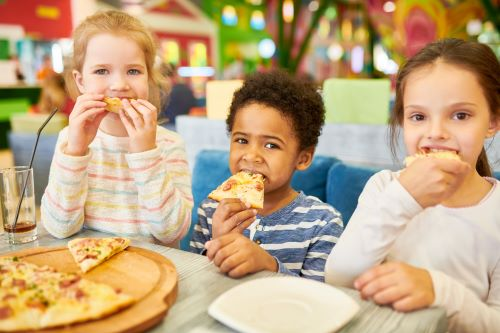 Three kids eating pizza