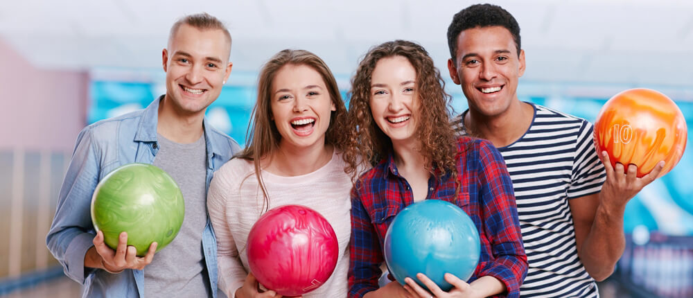 Four young adults posed with bowling balls.