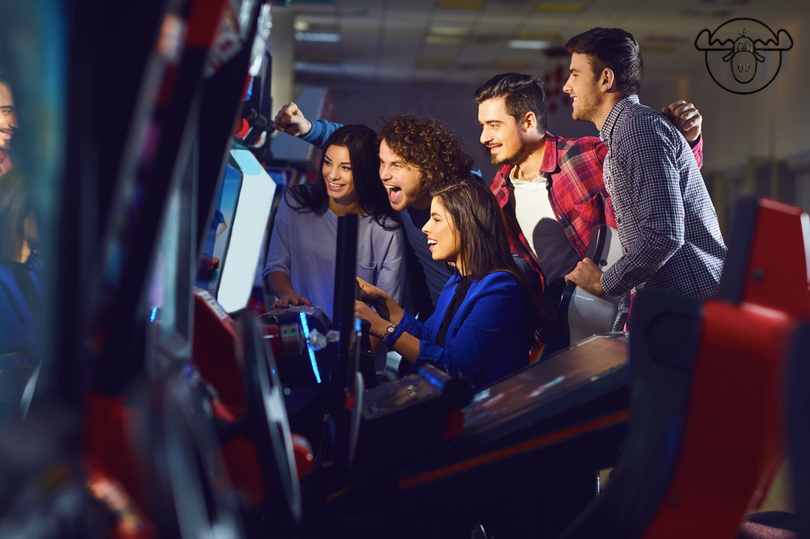 5 young adults playing racing arcade game