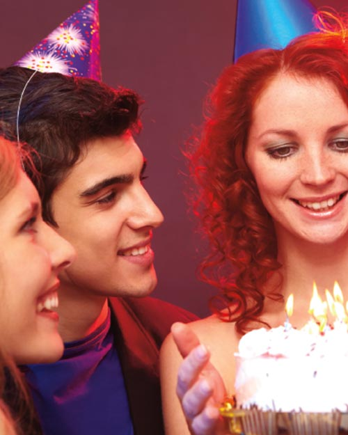 3 young adults around glowing candles for birthday party